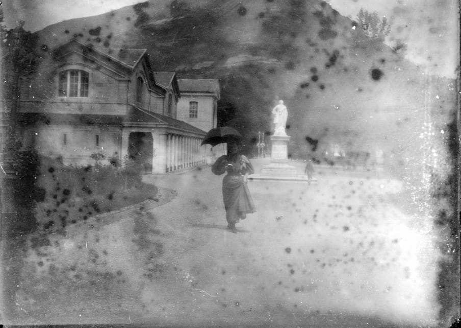Old damaged photograph of a woman standing with an umbrella