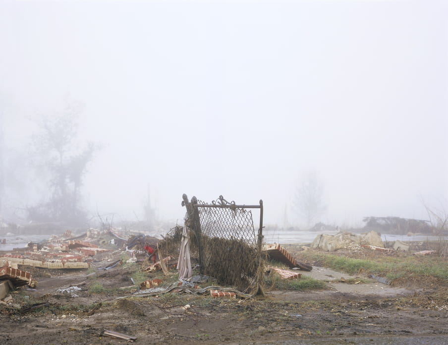 Photo of a place where a house used to be, with only a small fence still standing
