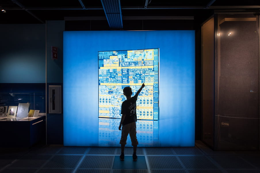 Photograph of a young person's silhouette standing and pointing to a blue screen wall of what looks like a yellow and blue aerial map of buildings. There are books on display in a glass cabinet to the left