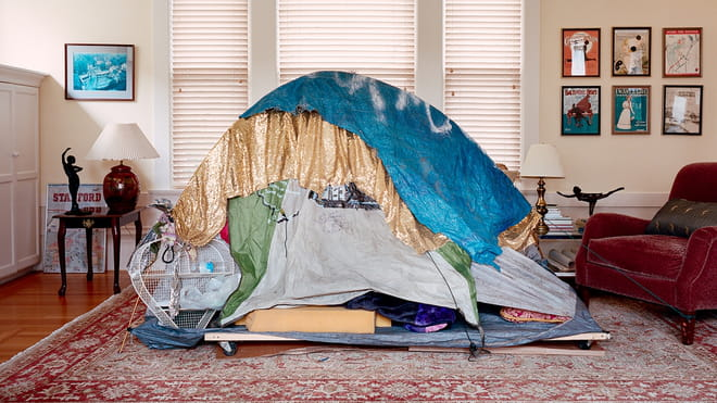 Photo of a living room of a middle or upper class house, with homeless shelter in it made up from different pieces of cloth and an old tent