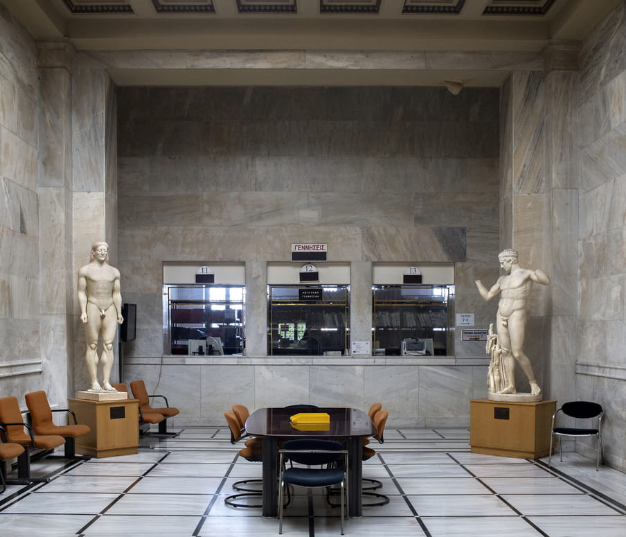 Two classical Greek statues in the corners of a large lobby of an office building in Athens.