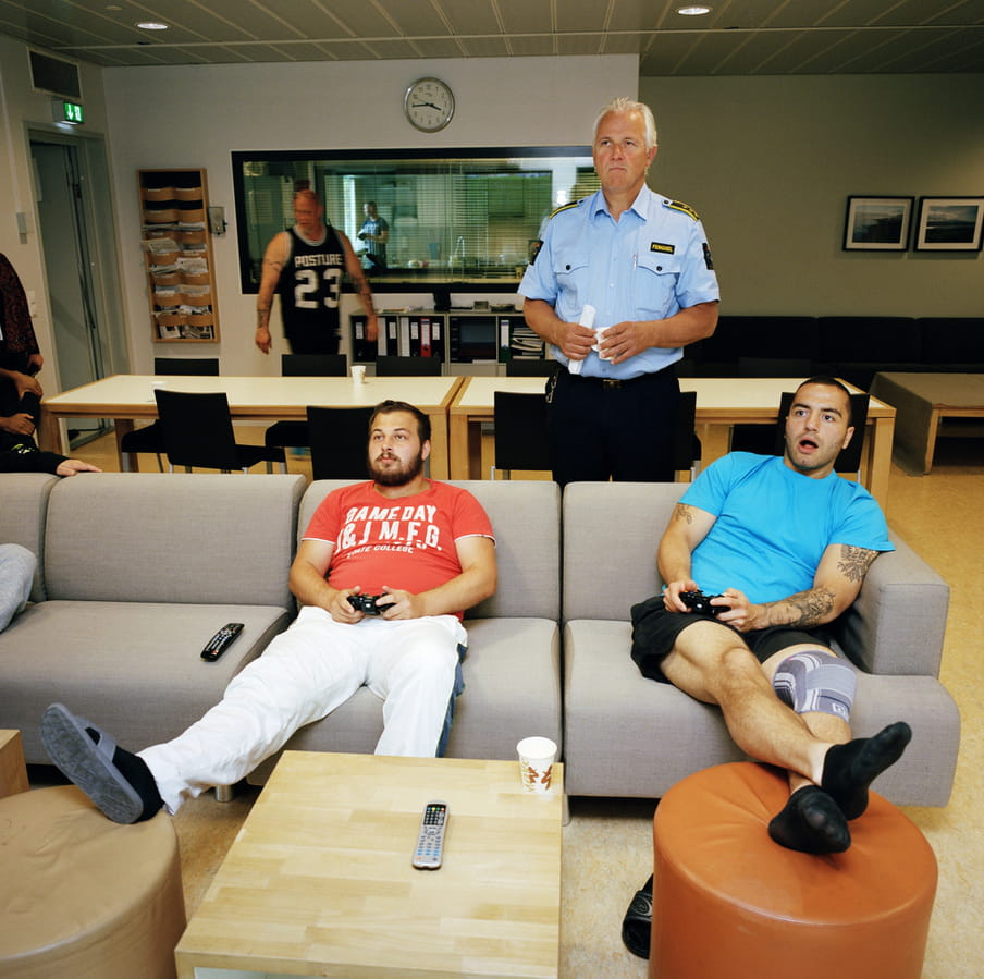 Four people in a photo, two of them in respectively red and light blue t-shirts on a light grey sofa holding black video game controllers, their legs up on soft stools in front of them. A man in prison guard uniform of a blue buttoned shirt and black trousers stands behind the sofa and them, looking in the direction they look in, holding a cup and a rolled up piece of paper. Beyond, a man in a black sports vest walks past two big white tables