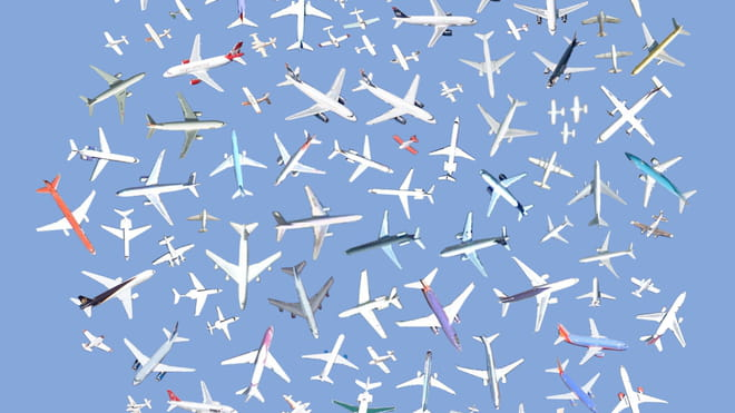 A profusion of planes, some white, others with touches of colours, arranged ob a blue background.