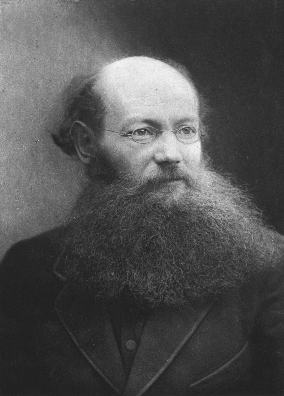 Black and white portrait of a man with glasses and a beard.