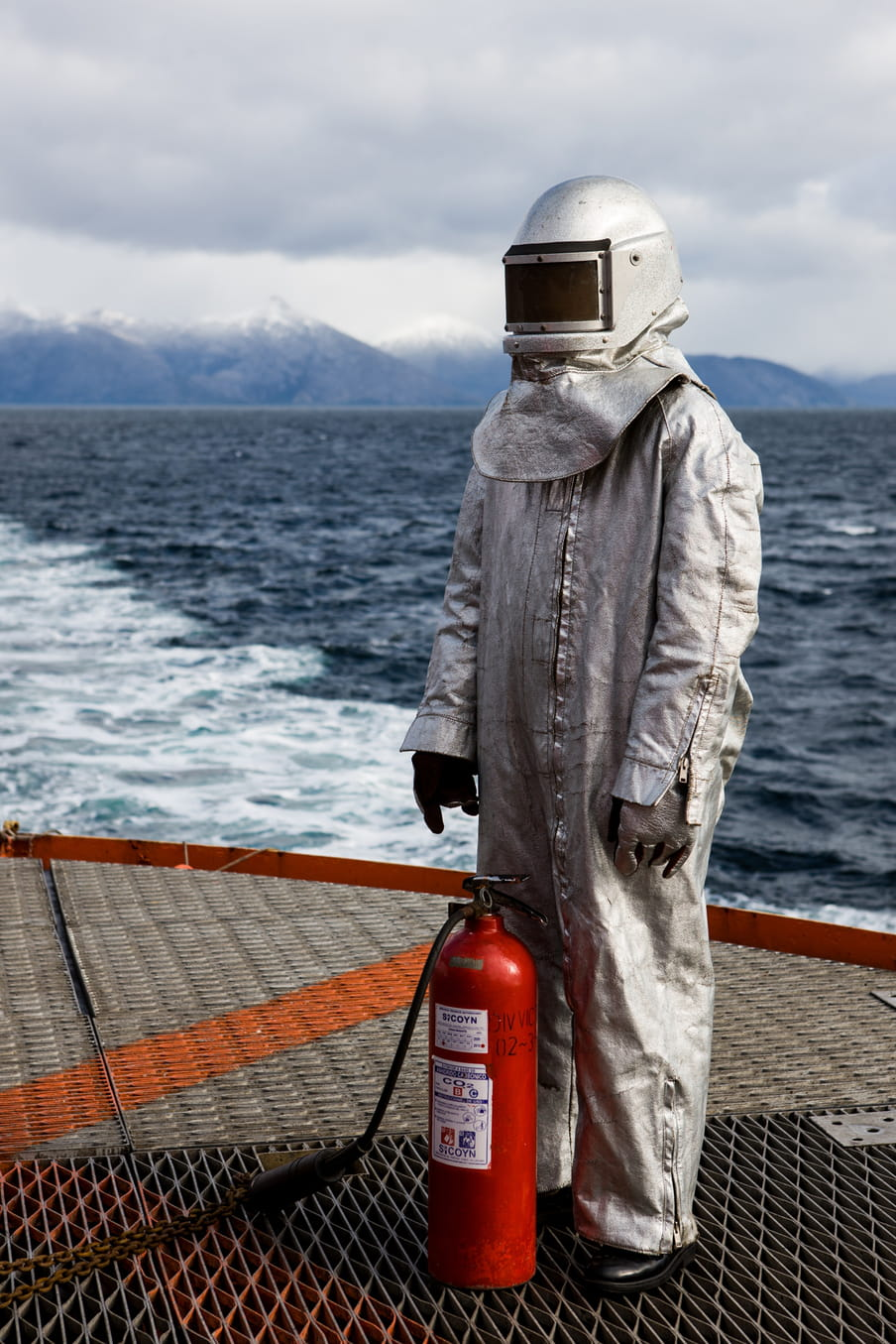 A person wearing a silver overall with helmet is standing on a boat, in front of a fire extinguisher.