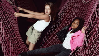 Photo of two young girls playing inside a pink net