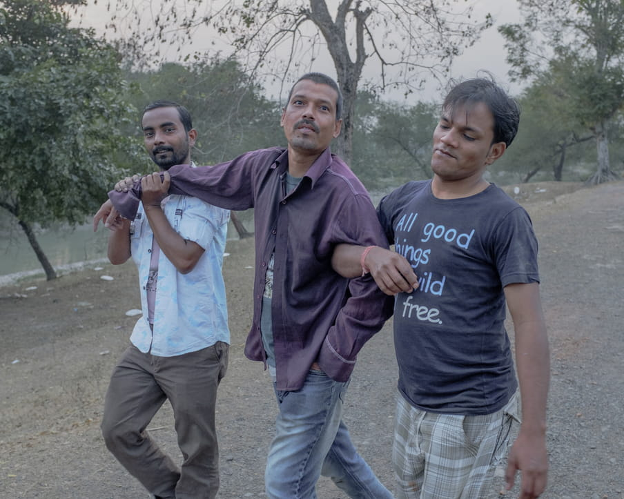 Three men are walking together on a gravel path. Some water and trees are visible in the background. The one in the middle wears jeans with a purple shirt. He looks at the camera, smiling slightly. The man on the left of the photograph looks at the camera with a small smile while holding the other man right arm at the rist with his two hands. The third man on the right of the frame looks down with a tiny smirk and he is holding the arm of the men in the middle.