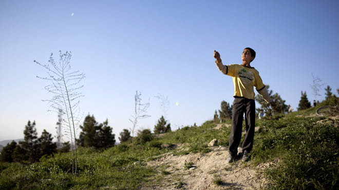A boy in a yellow jumper flying a kite - on a hill with blue sky in the background