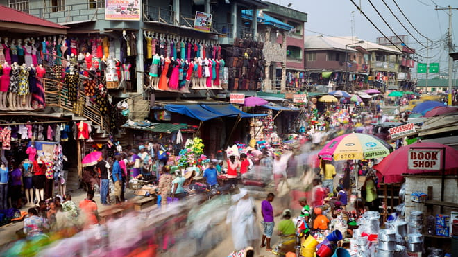 Photo of a busy street with a market on it, colourful merchandise hanging everywhere. It's shot with a long shutter speed so the people are blurred