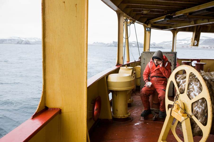 A man sitting a yellow and orange boat is wearing an orange overall. He's holding a white cup while on the phone.