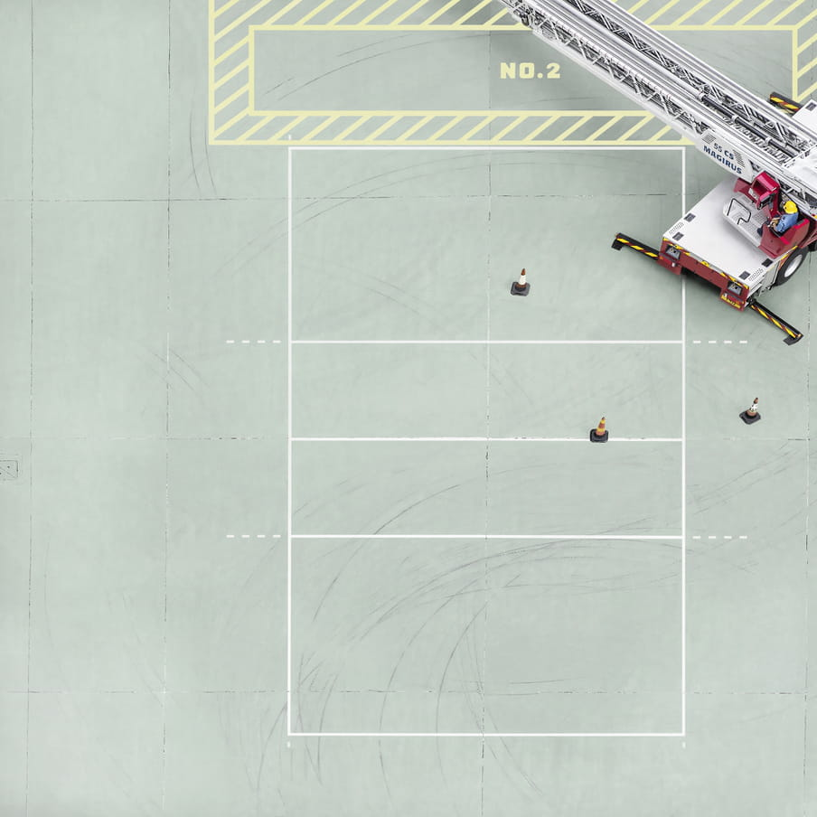 Photograph taken from above on a mint green court showing a firemen in a truck.