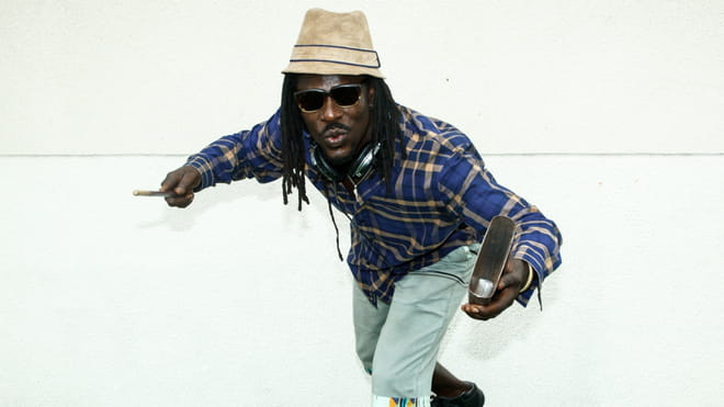 Photo of a figure in a blue and yellow checked shirt and light green pants, captured in movement in front of a white wall holding an instrument, arms out, mid-whistle