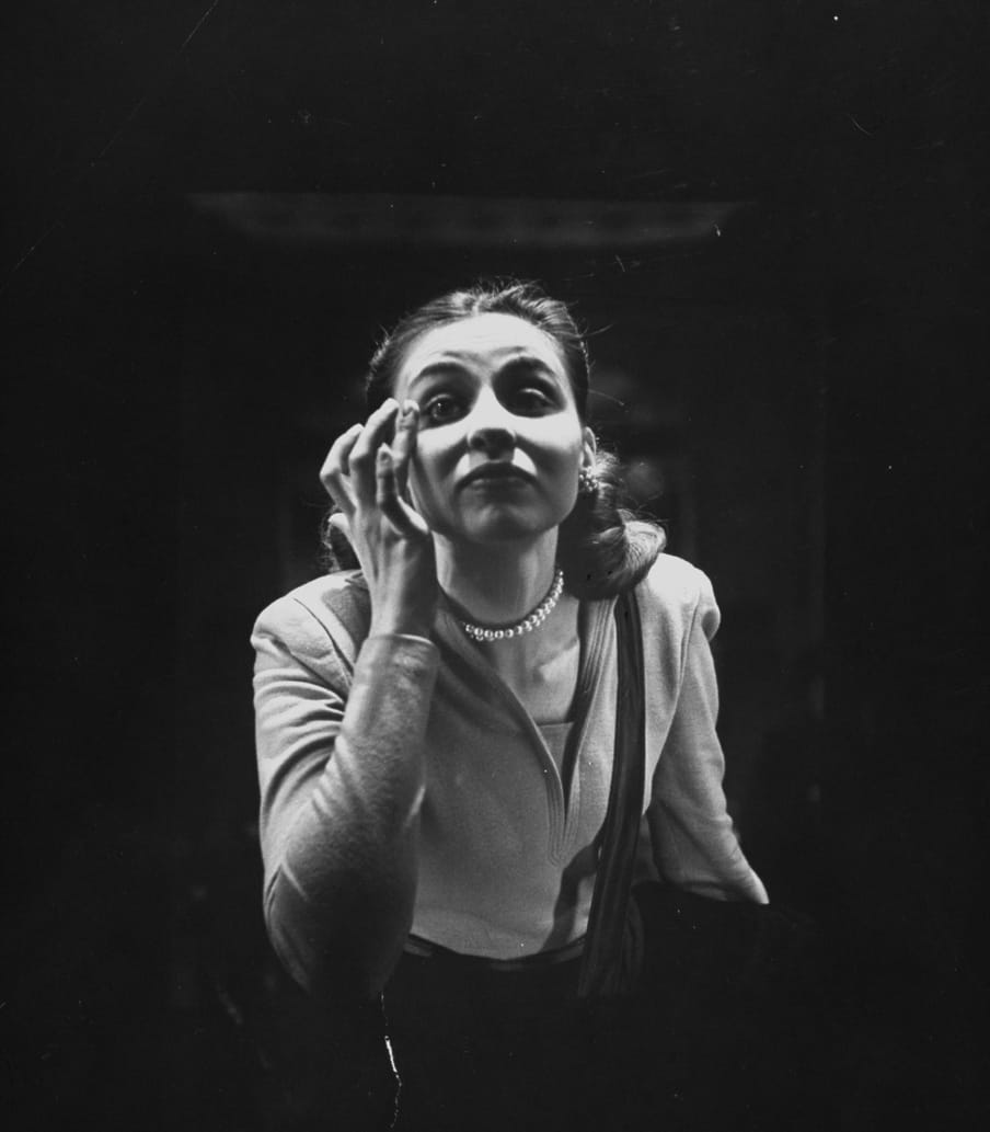 Old black and white photo of a woman checking her make up in a mirror, shot from the back of the mirror