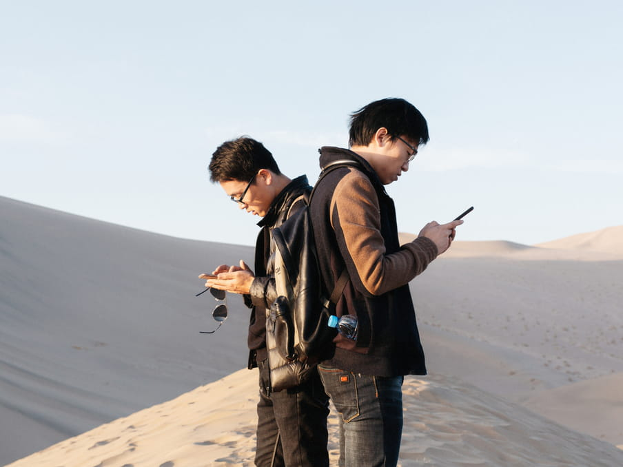 Photo of two young men looking at their phones