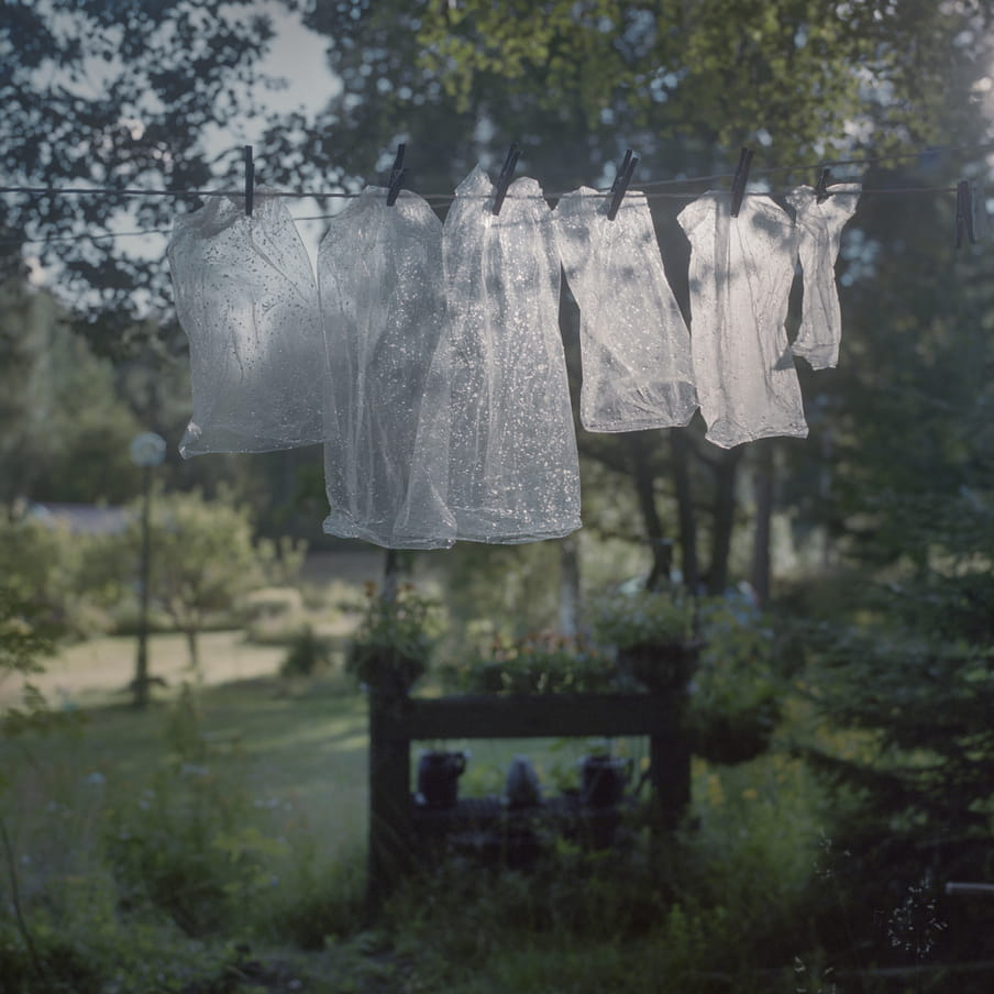 Photograph of plastic bags that are hanging on a line to dry in a green surrounding.
