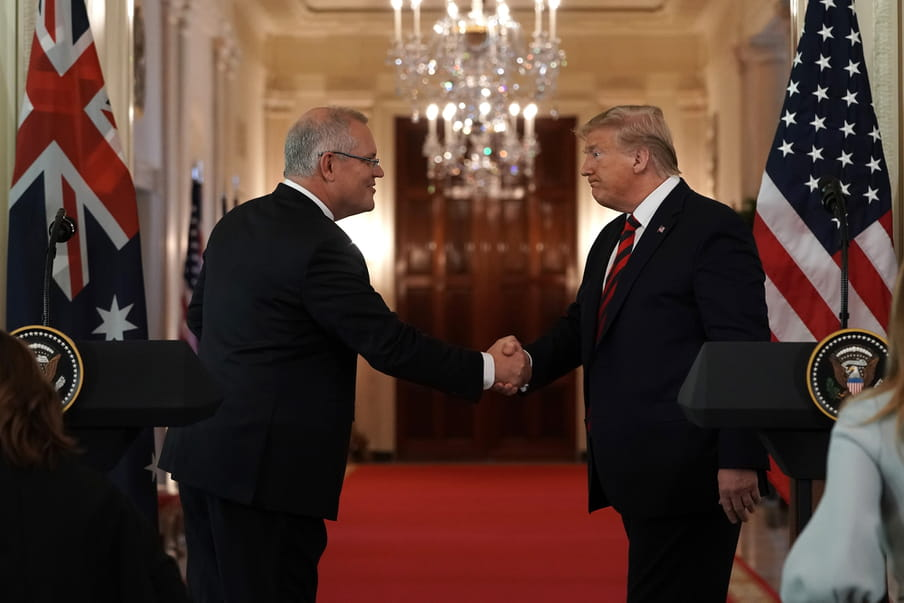 Two men wearing suits are shaking hands.
