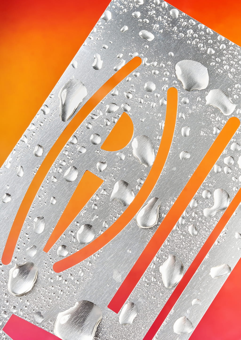 Photograph of a metallic stencil covered with drops of water on a pink and orange gradient background.