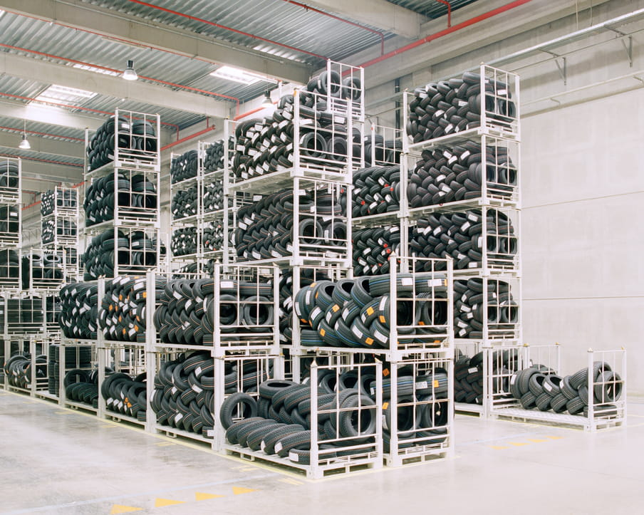Colour photograph of a warehouse showing shelves with piles of tires.