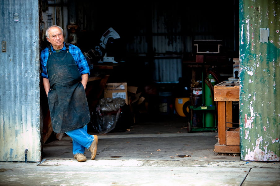 Photo of an older man standing in his workshop