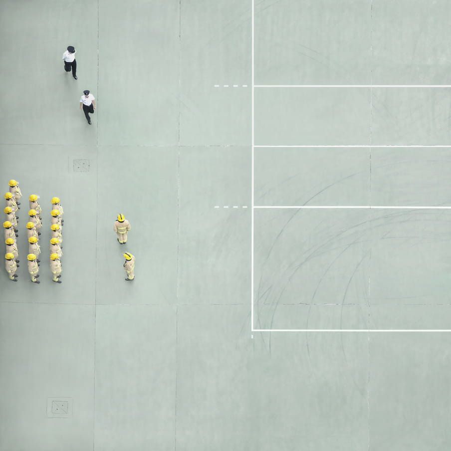 Photograph taken from above on a mint green court showing a group of firemen aligned and two police officers walking towards them.