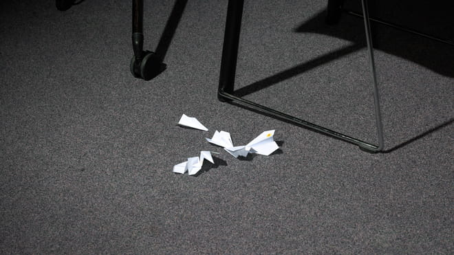 Photo of folded paper planes on a carpeted floor