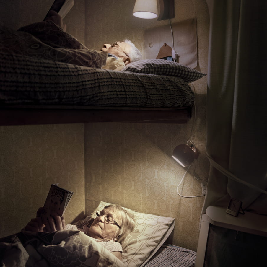 Photograph of an elderly couple reading in a bunk bed. Two small bed lights shine on the faces.