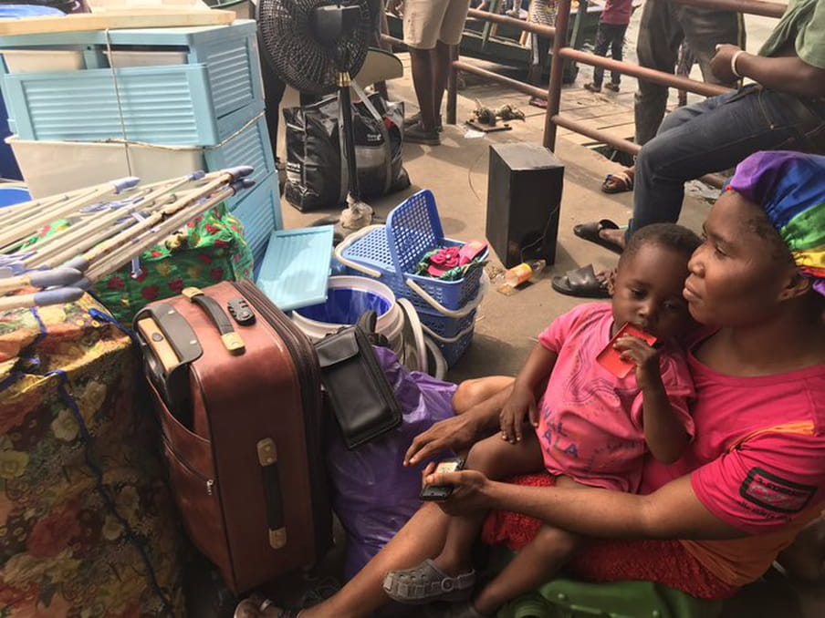 A woman and small child sit on the ground next to suitcases and other belongings.