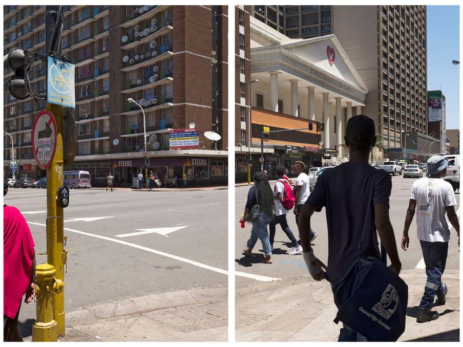 """A picture of people crossing a road - in the background a tall buildings and a sign of a local store that reads """"STEERS"""""""