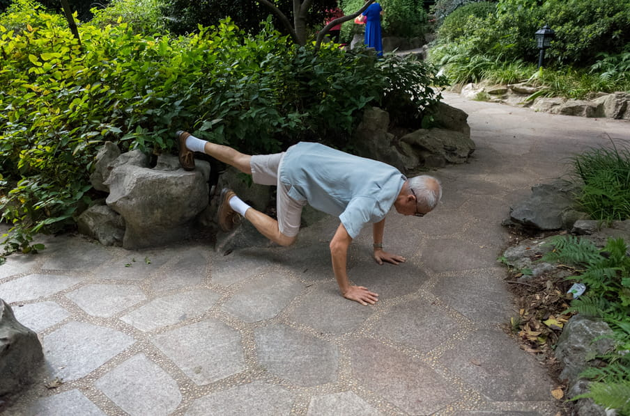 And old man in a park, leaning over a stone path to do stretching exercises.