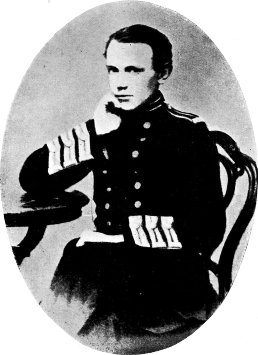Black and white archival photograph of a young man in uniform, sitting with his elbow on a table and his hand under his chin.