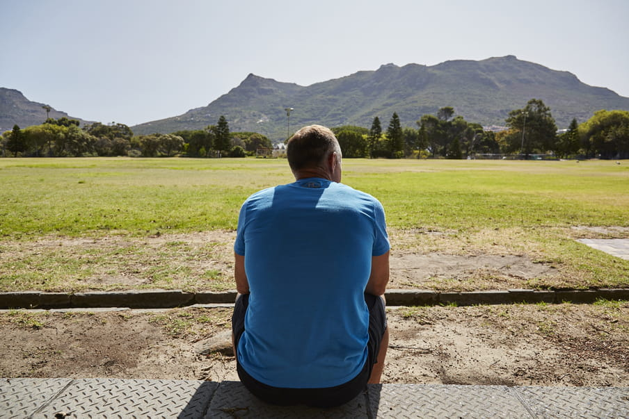 Photo of a man sitting down, looking at a field with mountains in the back