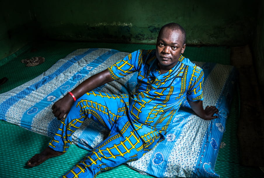 Photo of a man in a blue and yellow outfit sitting on a mattress on the floor