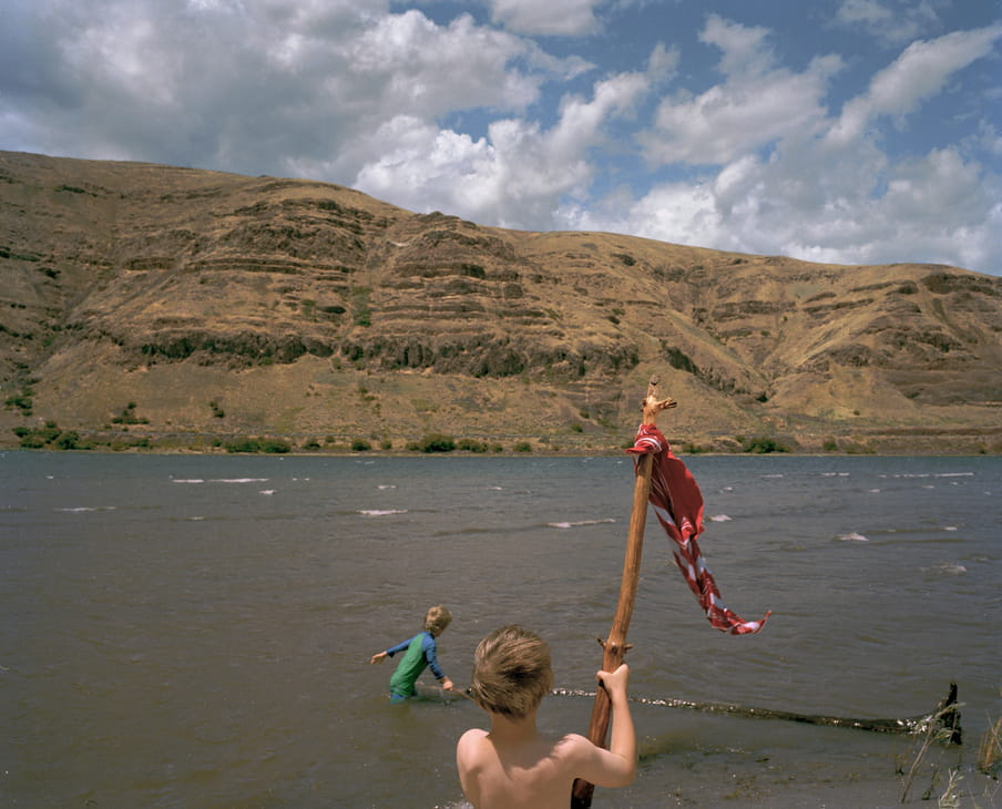 Photo of two kids playing in a river, one has a branch with a flag-like thing on it. Mountains are in the back.