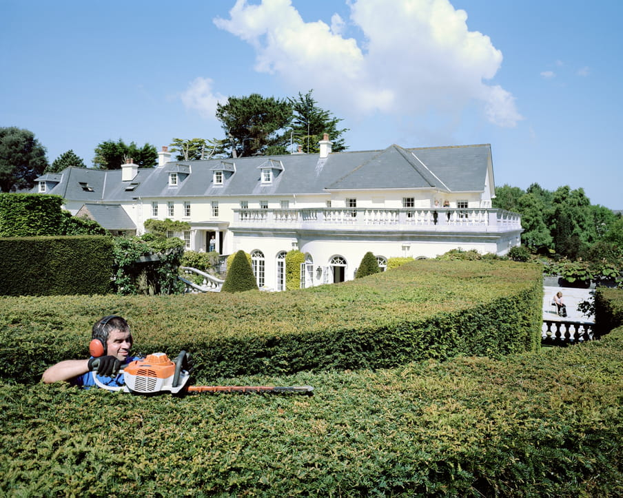 Picture of a large, white mansion and a gardener working in the yard