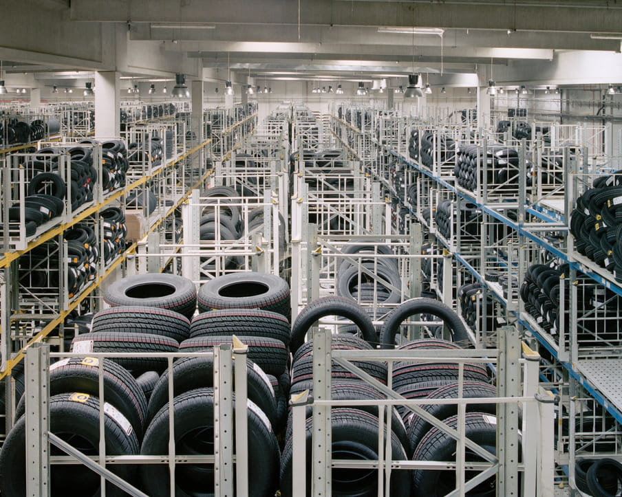 Colour photograph of a warehouse showing piles of tires.