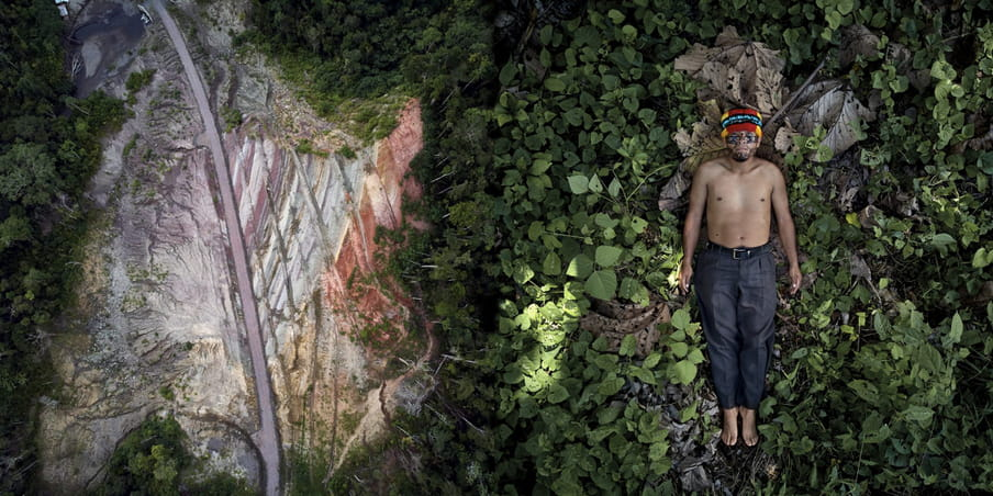 An aerial view (left) of a new road entering the Achuar territory, which looks like bones on the underside of a fish. A topless and barefoot man wearing a belt and long grey trousers (right), from the Achuar Nation, lies on sacred Indigenous land (we see green leaves), arms to his sides. He wears bright red, blue and yellow headgear.