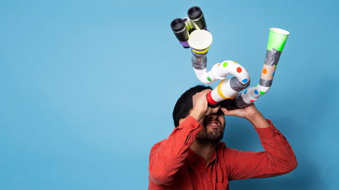 Man in front of a blue background - looking trough self-built binoculars, made from duck tape, toilet rolls, plastic and cups. It is warped and too long.