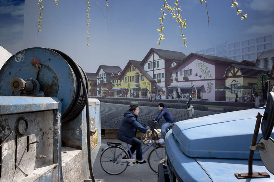 Two people cycling in opposite directions in front of a wall showing a photograph of a peaceful strip of houses.