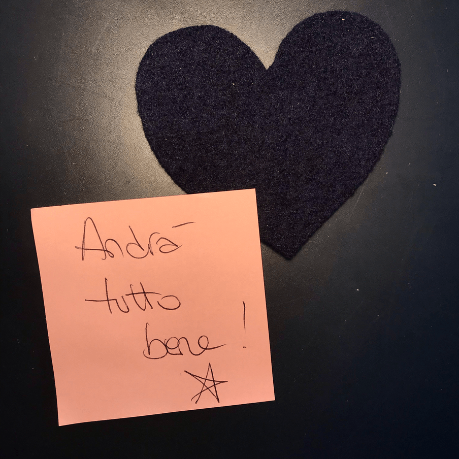 The image shows a dark blue felt hear and a handwritten pink post-it note that says: Andrà tutto bene.