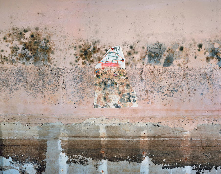 Photo of a wall with a drawing made by a child, destroyed by water damage.
