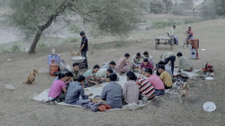Colour photograph of a group of men having a picnic on a plastic tarp on the ground. A man is standing next to them, stirring something in a big metallic bowl. A few trees and dogs are surrounding the scene. In the background, two men on bicycle are looking at the group.