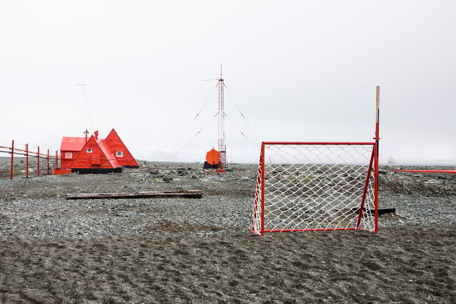A football net stands in the right side of the frame. On the left are triangular shaped buildings and an antenna is standing in the middle.