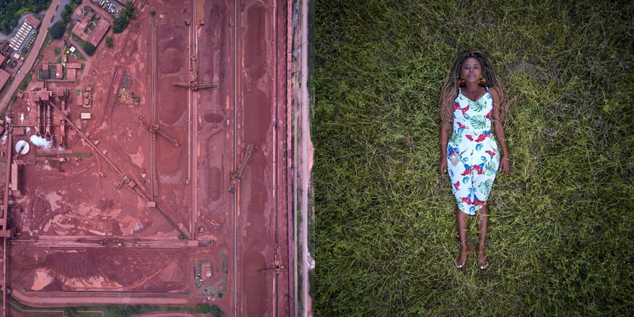 On the right, aerial photo of a human female figure lying face up on the grass, barefoot, in a white, blue and red flowery dress and big orange earrings. On the left, aerial photo of a red-tinged bauxite mine