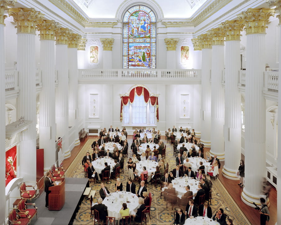 Picture of a large hall with roman white and gold columns, and about twelve round tables with white table cloths, people around it, looking at one man on a stage speaking