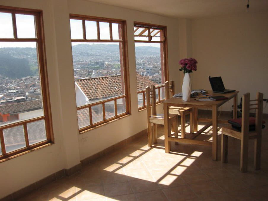 A photograph of the correspondent's apartment in Quito showing a table with four chairs and a vase with flowers, and on the left the picture window with a view of the outside rooftops.
