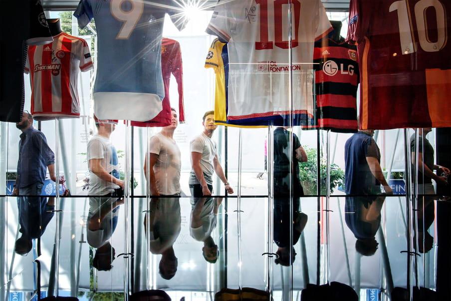 Photo of people visiting a football club museum and looking at football teams' T-shirts