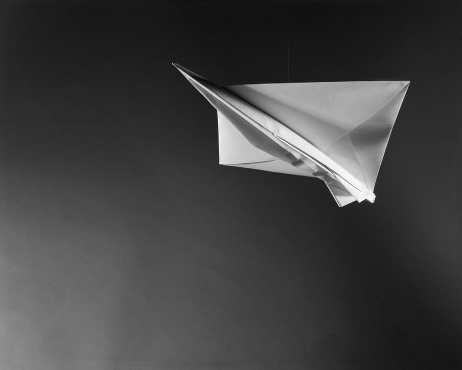 Black and white photo of a white paper plane, nose up in flight, to the top right of the image