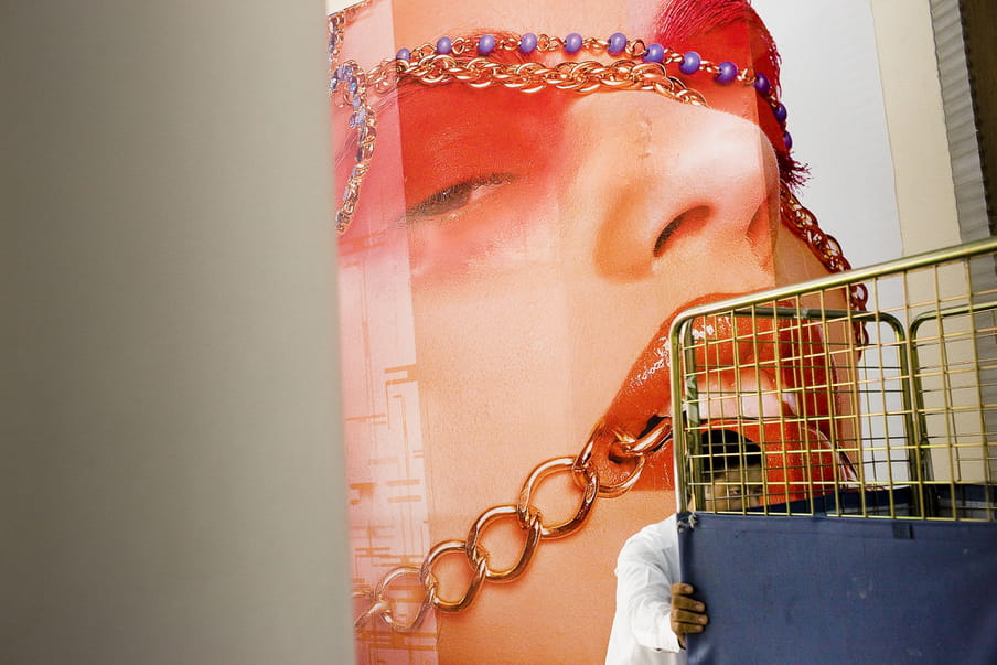 A man in white is pushing a high cart in front of a huge poster of a women's face with an intense make up and necklaces around her mouth, eyes and forehead.