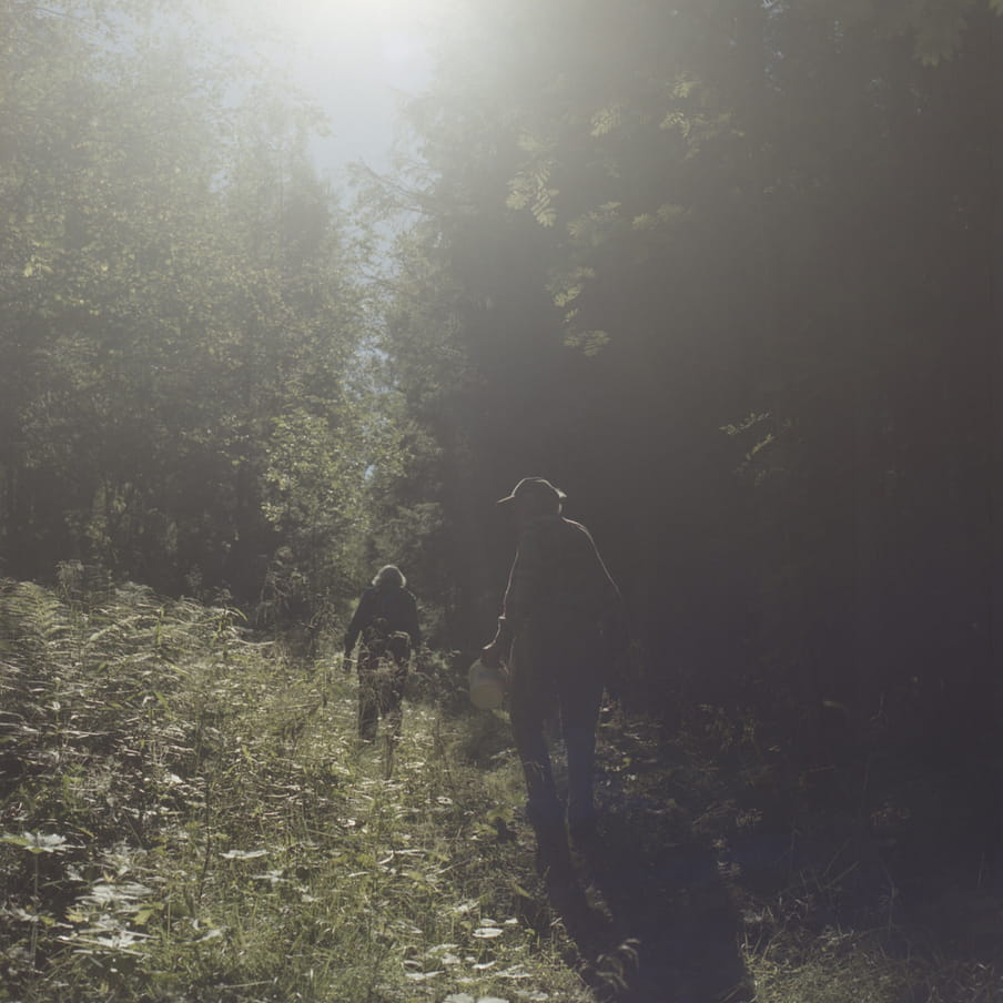 Photograph of two silhouettes of people in a forest with sun beaming through the middle.