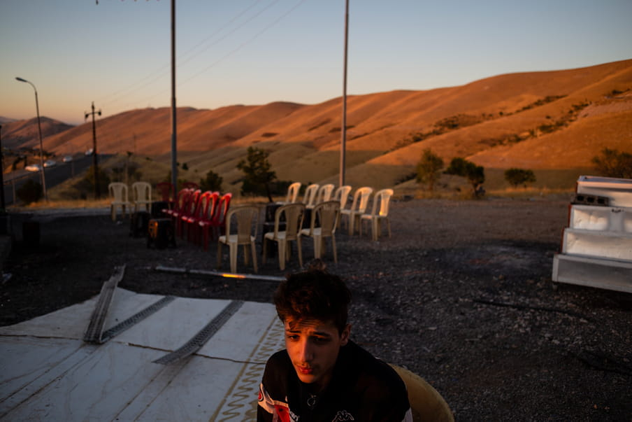 Photograph with a man at the centre and, in the background, a desert landscape with chairs
